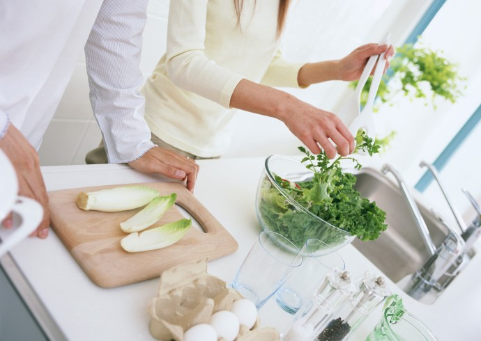 Couple cooking green, leafy foods in their kitchen