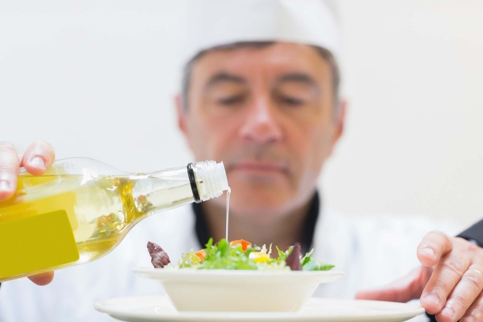 Chef pouring olive oil onto fresh salad