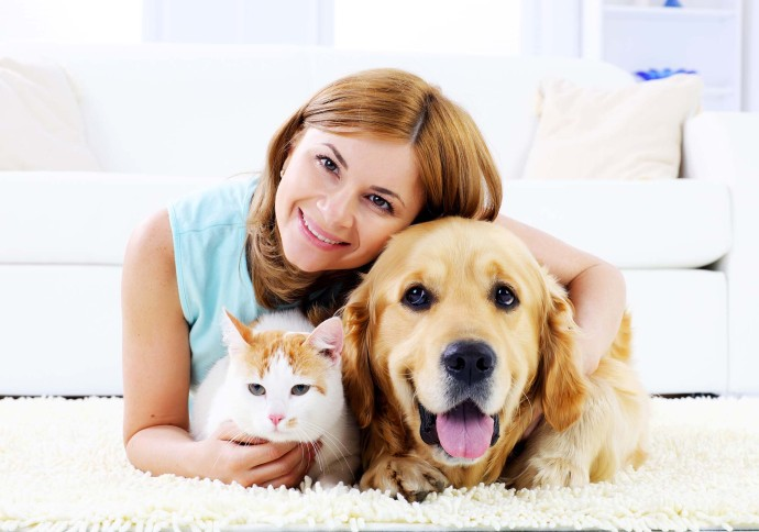 Woman laying with dog and cat on floor