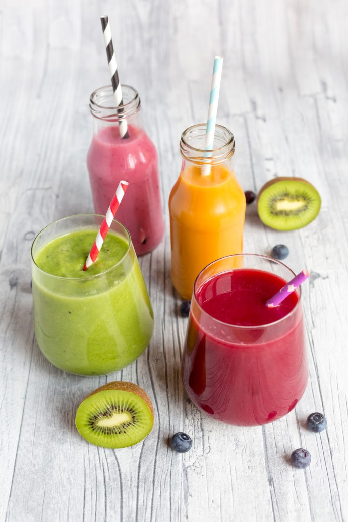 Colorful fruit smoothies with paper straws