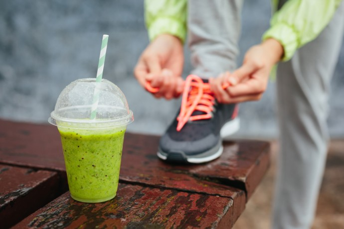 Green smoothie and person tying shoe