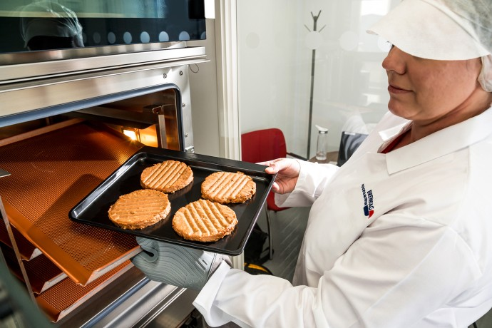 Chef placing meat patties into oven